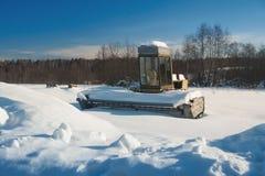 Alter Mähdrescher ohne Arbeit auf dem Gebiet deckte Schnee ab Stockbilder