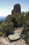 Alter Mühlstein, der unter einem Zutageliegen von roten Felsen an La-Col. De la Pierre du Coucou arbeitet Stockfotografie