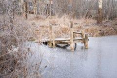 Alter malerischer und gemütlicher Pier auf dem gefrorenen Teich Lizenzfreie Stockfotos