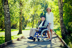 Alter Mann auf Rollstuhl und junger Frau im Park Lizenzfreie Stockfotos
