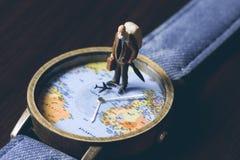 Alter Mann auf Uhren mit Weltkarte, Weinlese tonte Foto Weltreisefahne Ältere Reisendfigürchen Stockfoto