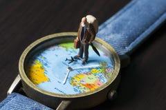 Alter Mann auf Uhren mit Weltkarte Weltreise-Fotofahne Ältere Reisendfigürchen Lizenzfreies Stockfoto