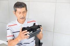 Alter Mann in den vr Wirklichkeitsgläsern virtueller Realität mit dem Spielen des Spiels stockbild