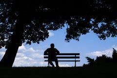 Alter Mann, der allein auf Parkbank unter Baum sitzt stockfotografie