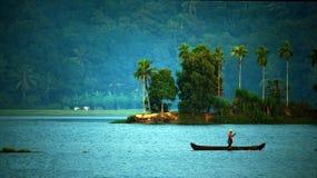 Alter Mann, der allein in einem Boot fischt stockbild