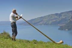 Alter Mann, der an Alpen-Horn mit Thun See im Hintergrund singt Lizenzfreie Stockbilder