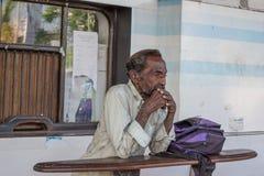 Alter Mann, der auf dem Bahnhof steht und denkt Stockbild