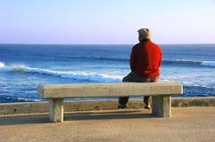 Alter Mann, der auf der Bank sitzt Stockfotos