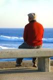 Alter Mann, der auf der Bank sitzt Stockbilder