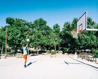 Alter Mann, der auf einem Basketballgebiet spielt lizenzfreie stockbilder