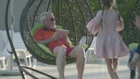 Alter Mann, der auf einem hängenden Stuhl sich entspannt im Hotelkomplex sitzt Nette Stellung des kleinen Mädchens nahe Großvater stock footage