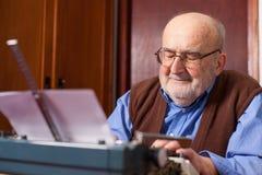 Alter Mann, der auf einer Schreibmaschine schreibt Lizenzfreie Stockfotografie