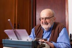 Alter Mann, der auf einer Schreibmaschine schreibt Stockfotos
