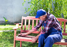 Alter Mann, der Bank im Garten repariert Stockfotos