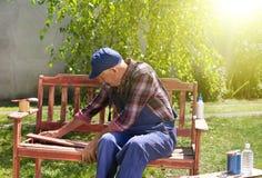 Alter Mann, der Bank im Garten repariert Lizenzfreies Stockbild