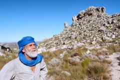 Alter Mann in der beduinischen Kleidung betrachtet Berge Stockfotografie