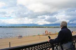 Alter Mann, der den Weinleseregenschirm weit schaut hält Lizenzfreies Stockbild