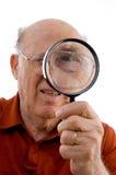 Alter Mann, der durch Objektiv schaut Stockbilder