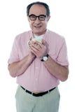 Alter Mann, der eine Kaffeetasse anhält lizenzfreie stockbilder
