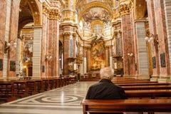 Alter Mann, der in einer katholischen Kirche in Rom betet Lizenzfreie Stockfotografie