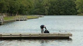 Alter Mann, der für die Fischerei auf dem Pier sich vorbereitet stock video footage