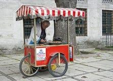 Alter Mann, der gebackene süße Kastanien verkauft Stockbild