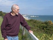Alter Mann, der heraus in dem Ozean anstarrt stockfoto