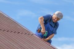 Alter Mann, der an der Hitze auf einem Dach eines Hauses mit Elektroschrauber, keine Sicherheitsvorrichtungen tragend, Arbeitskle Lizenzfreies Stockfoto