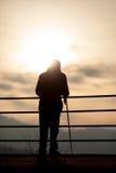 Alter Mann, der im Sonnenuntergang mit Stock steht Stockbilder