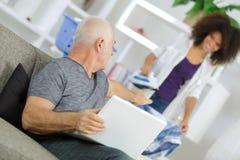 Alter Mann, der Laptop bei der Unterhaltung mit Assistenten verwendet Stockfotos