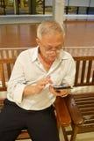 Alter Mann, der Mobile spielt stockbilder