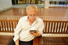 Alter Mann, der Mobile spielt stockbild