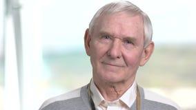 Alter Mann, der neugierig, unscharfer Hintergrund schaut stock video