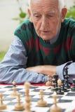 Alter Mann, der Schach spielt Lizenzfreie Stockfotos
