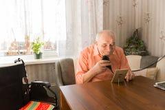 Alter Mann, der seinen Bart mit Rasiermesser am Tisch säubert Stockfotografie