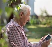 Alter Mann, der Tablette betrachtet Stockfotografie