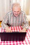 Alter Mann, der Technologie einsetzt Stockbild