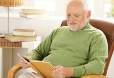 Alter Mann, der zu Hause das Lesen sitzt Stockfotos