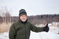 Alter Mann draußen Blume im Schnee Lizenzfreies Stockfoto