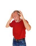 Alter Mann erschrocken mit den Händen auf Kopf Stockbild