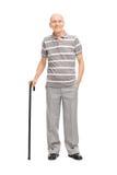 Alter Mann im Polohemd, das einen Stock und eine Aufstellung hält Lizenzfreies Stockfoto