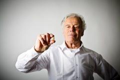Alter Mann im Weiß und in der Pille Stockfoto