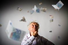 Alter Mann im Weiß und im Euro Stockfotos