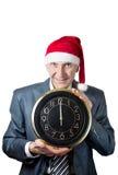 Alter Mann im Weihnachtshut, der ein großes Borduhr isola anhält Stockfoto