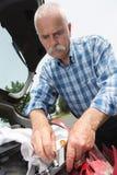 Alter Mann installiert Rücklicht auf Fahrzeug Stockbild