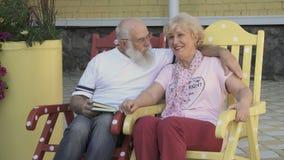 Alter Mann liest ein Buch eine Frau und küsst sie in der Backe und entspannt sich in den Schaukelstühlen stock footage