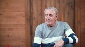 Alter Mann mit dem grauen Haar, das vor Kamera sitzt und Gespräch mit jemand nimmt Hölzerner Hintergrund 4K Lizenzfreie Stockfotos