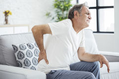 Alter Mann mit den rückseitigen Schmerz stockbilder