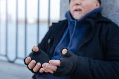 Alter Mann mit den wunden Fingern schnorrend für Lebensmittel Lizenzfreie Stockfotos