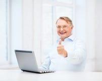 Alter Mann mit der Laptop-Computer, die sich Daumen zeigt Lizenzfreie Stockfotos